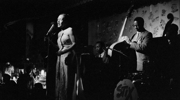 Billie Holiday performing on stage with her band